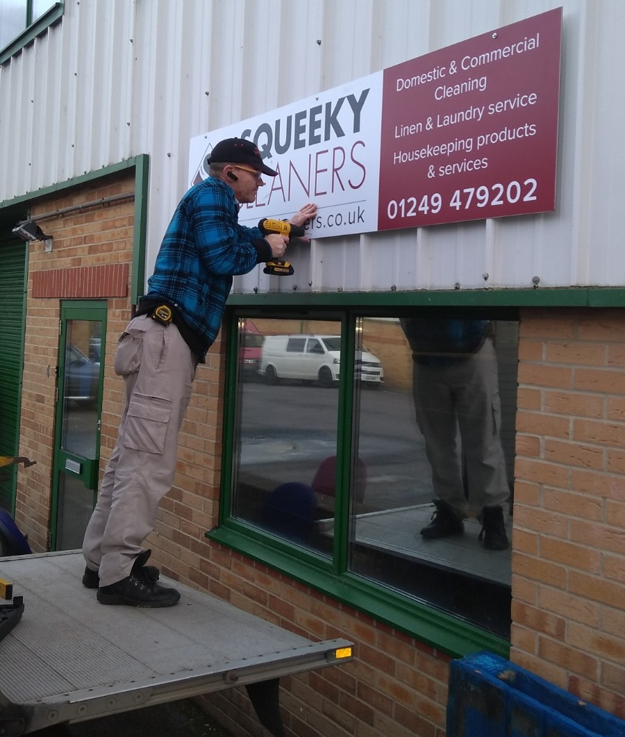 handyman putting up squeeky cleaners sign